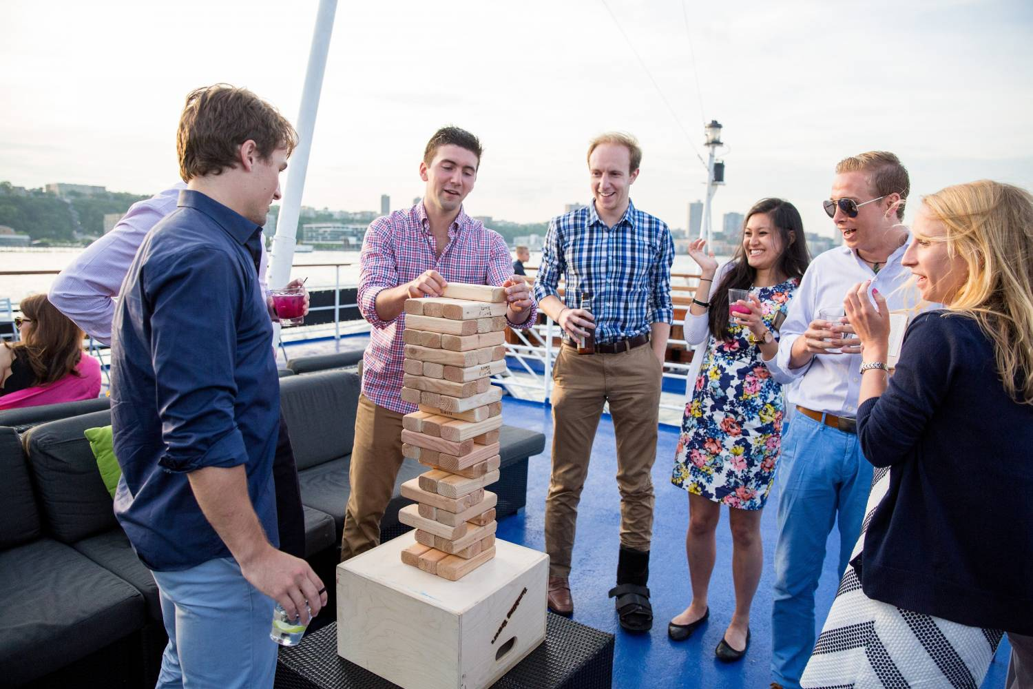 Adults somehow managing to play jenga on a boat