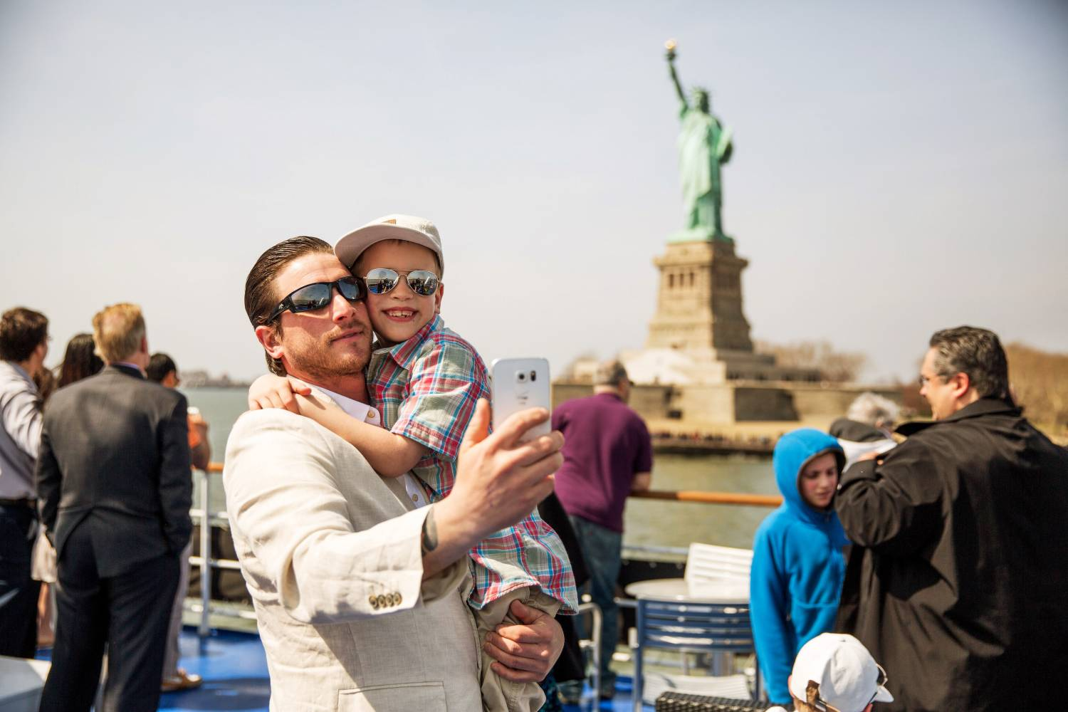 Patrons taking a selfie with statue of liberty in the background on a Spirit of New York boat