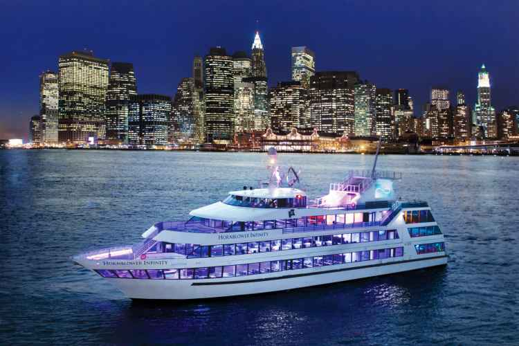 Hornblower Infinity in the east river with view of manhattan